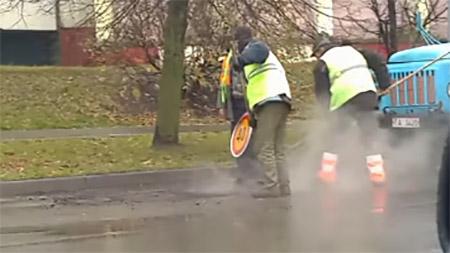 Дорожные рабочие в Бобруйске трамбуют свежий асфальт дорожным знаком